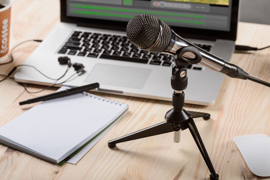 An ordinary set for voice work. Professional black mic on a holder, headphones and modern laptop with special applications. A pen with a notebook for notes.